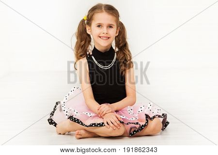 Portrait of happy little girl in beautiful dress and bead necklace, sitting on the floor against blanked background