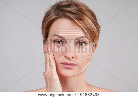 Face of woman with perfectly clean skin and massage facial lines. Skin Care. Face lift anti-aging treatment