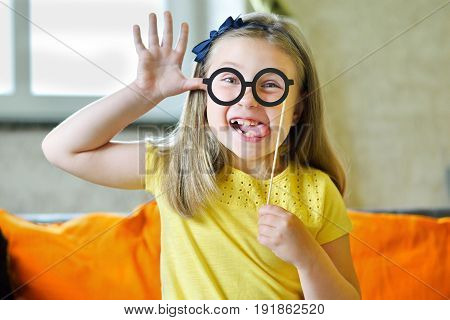 Little Girl Making Face With Funny Glasses And Showing Her Tongue