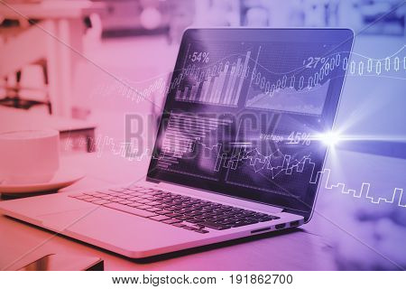 Side view of laptop with digital business charts placed on desktop with coffee cup. Toned image. Accounting concept