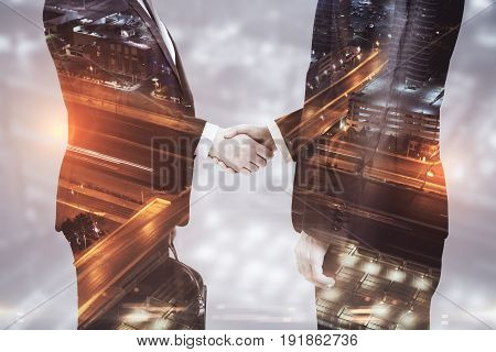 Side view of handshake on night city background. Teamwork concept. Double exposure