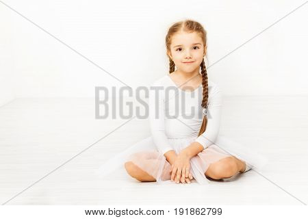 Portrait of Caucasian girl wearing white dancewear sitting on the floor of ballet studio with blanked background