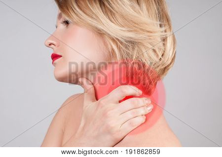 Young woman with neck pain. Woman holds a hand on neck massaging her shoulder