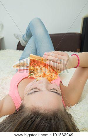 fun hungry girl eats pizza lying at sofa