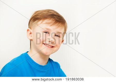 Close-up portrait of cheerful seven years old boy in blue t-shirt posing against blanked background