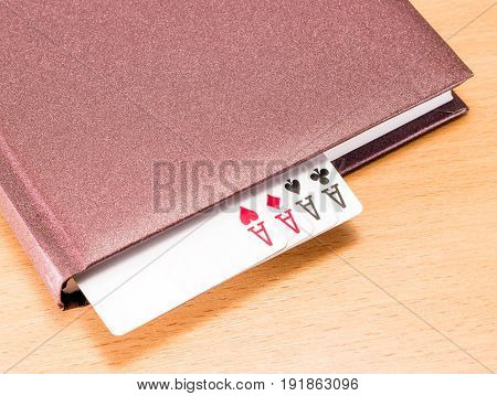 Four aces peeking out from a solid diary is a very strong combination in poker symbolizes success in business