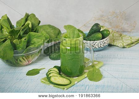 Mason jar mugs filled with fresh green spinach and cucumber smoothie on light blue wooden background. Healthy food and vegetarian concept.