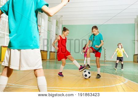 Portrait of preteen boys and girls training football in school sports hall
