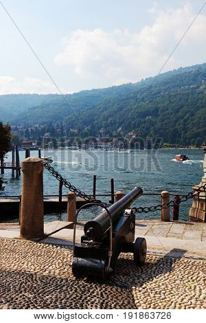 The ancient gun decorates quay in beautiful well-groomed park on island Izola Bella