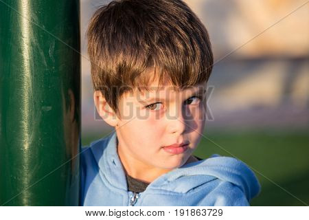 Very beautiful six year old boy with green eyes playing in the playground. Beautiful sunny winter day