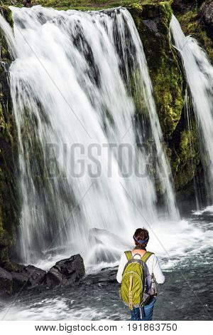 Elderly woman -  traveler with a large backpack admiring the powerful jets of the waterfall Kirkjoufellfoss. Summer in Iceland. Concept of exotic and extreme tourism