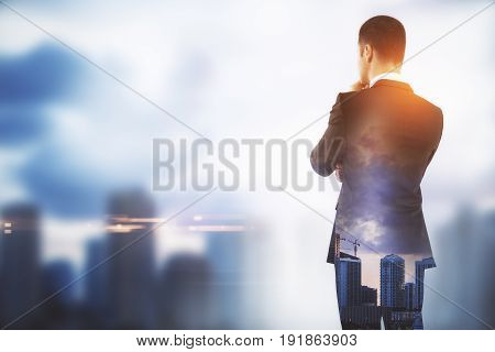 Side view of young businessman on blurry city background with copy space. Tomorrow concept. Double exposure