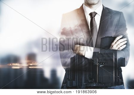 Young businessman with folded arms standing on city background with copy space. Employer concept. Double exposure