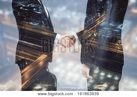 Side view of handshake on night city background. Partnership concept. Double exposure