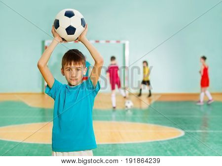 Portrait of 12 years old boy, tossing soccer ball during football match in school gymnasium