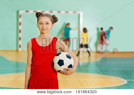 Portrait of happy 12 years old girl, football player, standing with ball in sports hall during the match