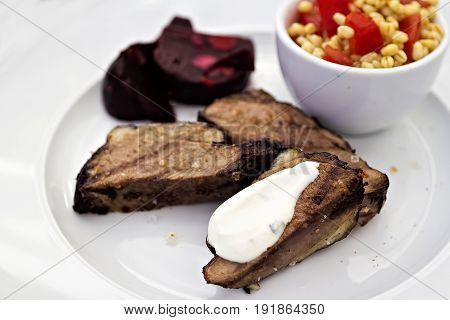 Lamb steaks with garlic sauce, beetroots and bulgar salad