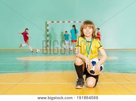 Portrait of smiling preteen boy, soccer team captain, standing on knee in futsal with ball