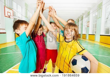 Portrait of preteen boys and girls, happy football winners, giving high five in sports hall
