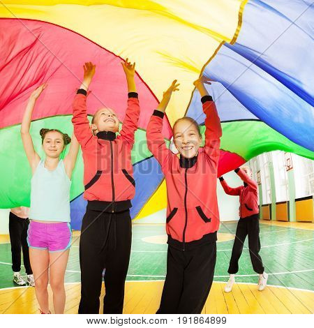 Three happy preteen girls hiding under the rainbow parachute's canopy during sports festival in school gymnasium