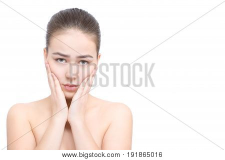 sad young woman with pain touching her teeth, isolated in white