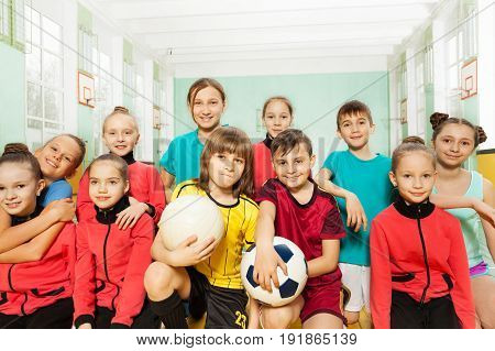 Group of soccer team, preteen boys and girls, sitting together in school gym