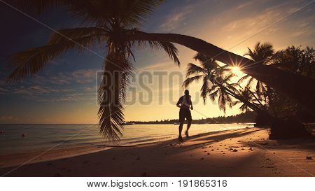 Sea sunrise. Man runing on the tropical island beach Punta Cana.