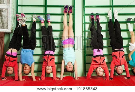 Portrait of sporty preteen boys and girls trying to hold straight handstand during physical education lesson
