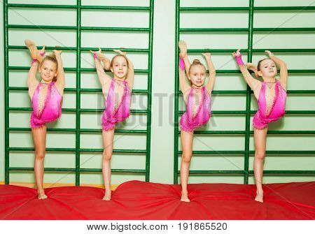 Group of four preteen girls stretching near wall mounted gym ladder during gymnastic class