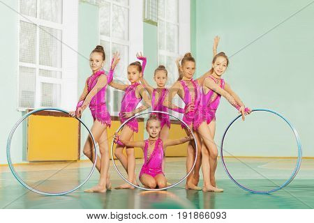 Rhythmic gymnastic team of 11-12 years old girls posing with hoops in sports hall