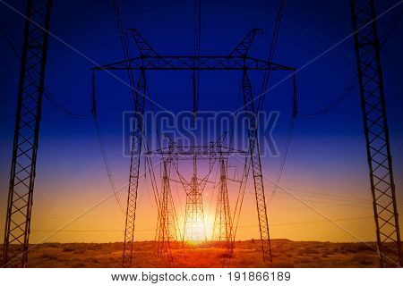 Construction of power lines against the backdrop of the setting sun