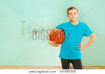 Portrait of happy 12 years old girl, basketball player, standing with ball in sports hall