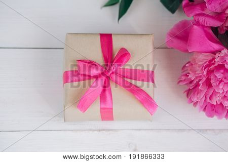 Beautiful fresh pink peony flower with gift box on wooden background. Peonies summer.