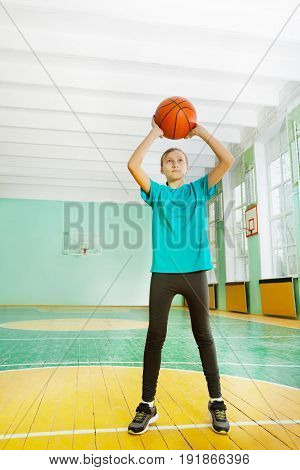 Full-length portrait of 12 years old girl tossing basketball in rim during physical education class