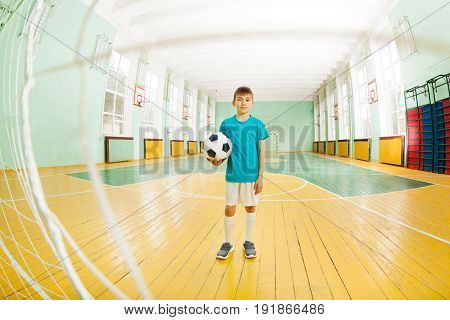 Full-length portrait of 12 years old boy in football uniform, standing in school gymnasium, holding soccer ball, shot through the gate net