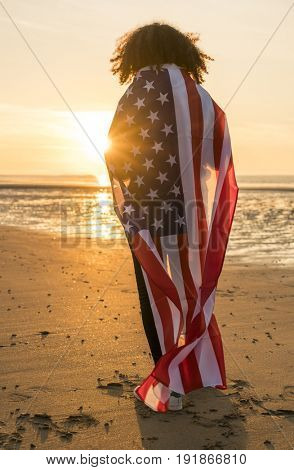 Rear view of mixed race African American girl teenager female young woman on a beach wrapped in USA stars and stripes flag in golden sunset evening sunshine