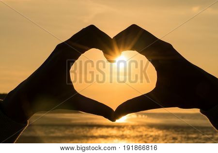 Hand heart frame shape silhouette made against the sun & sky of a sunrise or sunset on a deserted empty beach