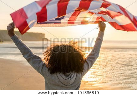 Rear view of mixed race African American girl teenager female young woman on a beach holding USA stars and stripes flag above her head in golden sunset evening sunshine