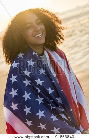 Beautiful happy mixed race African American girl teenager female young woman wrapped in the stars and stripes US flag on a beach smiling laughing with perfect teeth in golden sunset evening sunshine