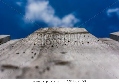 close up of an old wood fence viewed from below when looking up at a blue sky with white clouds on a warm summer morning