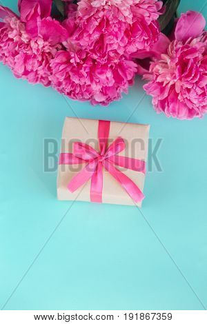 Beautiful fresh pink peony flower with gift box on mint background. Peonies summer.