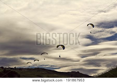 Line of parachutes on the cloudy sky