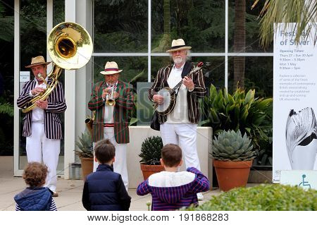Wisley, Surrey, Uk - April 30 2017: Trad Jazz Trio Of Musicians Playing Outside The Tropical Glassho