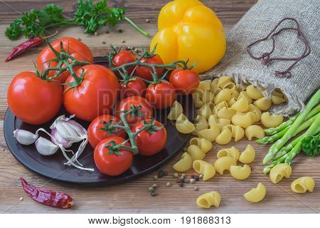 Ingredients for traditional italian cuisine - dry pasta, vegetables, different fresh tomatoes, garlic, asparagus, yellow bell pepper. Concept of vegetarian and healthy food. Top view