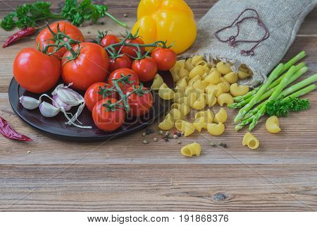 Italian food cooking ingredients on wooden background, dry pasta and vegetables, different varieties of fresh tomatoes, garlic, asparagus, bell pepper. Concept of italian cuisine, vegetarian and healthy food, copy space