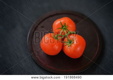 Three fresh red ripe tomatoes with water drops on branches, wooden plate, black background. Selective focus. Top view. Concept of vegetarian and healthy food. Low key. Copy space