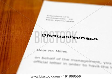 A letter on a wooden table - dissuasiveness