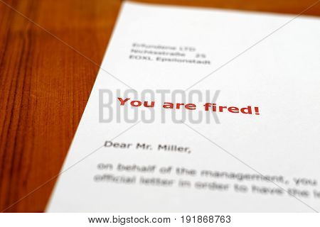 A letter on a wooden table - you are fired