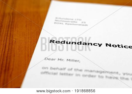 A letter on a wooden table - redundancy notice