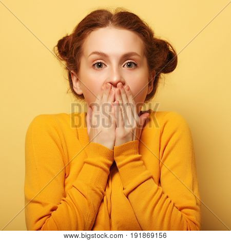 Beautiful young surprised redhair woman over yellow background